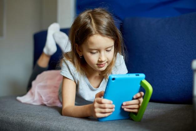 Милая маленькая девочка, лежащая на диване, малыш, увлекающийся технологиями, наслаждается онлайн-игрой на цифровом планшетном компьютере, использует приложения, просматривает информацию в интернете дома,