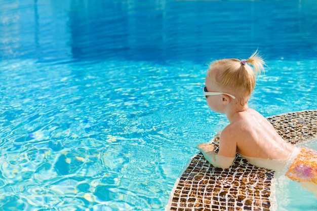 Cute little girl lying on the side of the pool and looking at the blue water. top view. copy space.