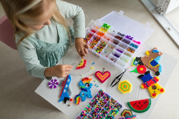 Cute little girl makes a toy with thermo mosaic
