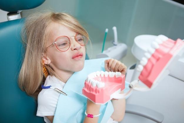 歯科医院で大きな顎のモデルを見て、変な顔をしているかわいい女の子