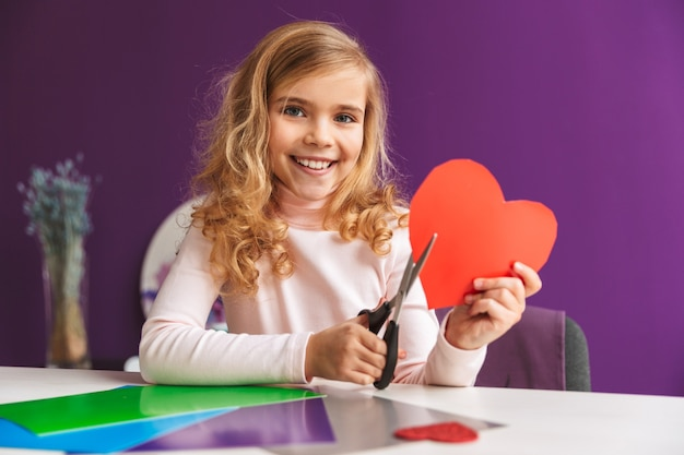 Cute little girl making a heart from paper at the table