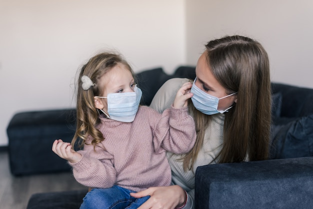 Cute little girl and mother wearing face mask, sitting on bed at home, consoling sad preschool daughter