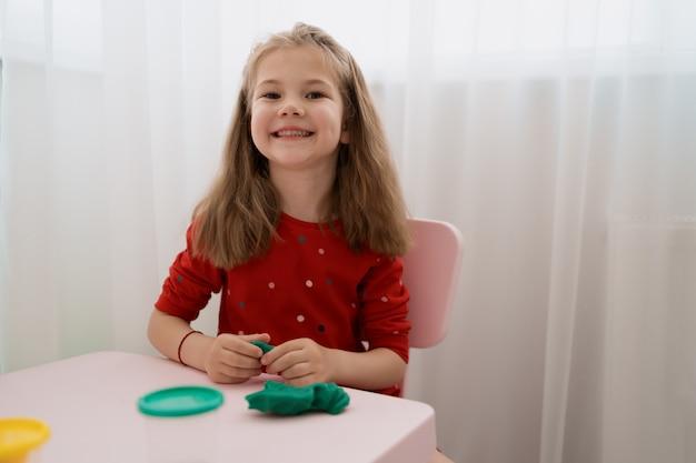 テーブルの上の粘土からかわいい女の子金型