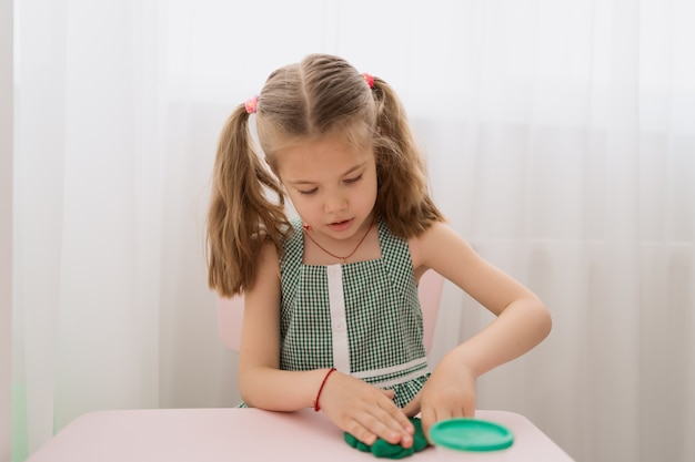 Cute little girl moulds from plasticine on table