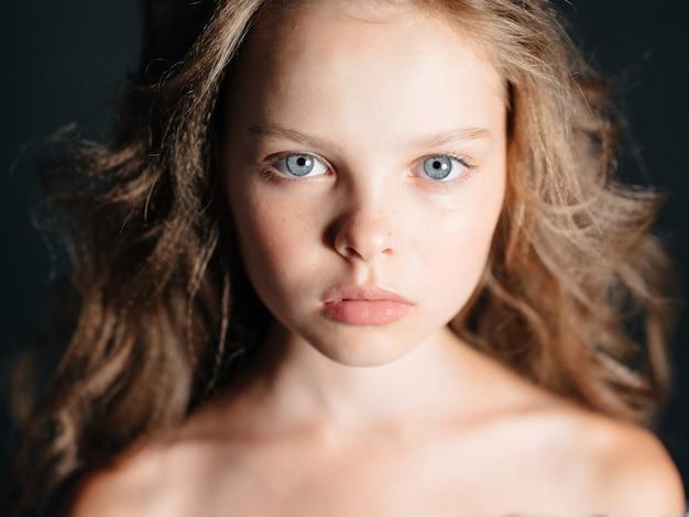 Милая маленькая девочка голые плечи темный фон красивое лицо крупным планом