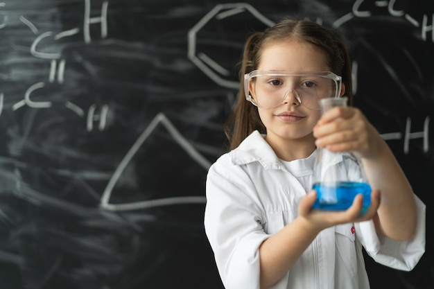 화학 수업 시간에 칠판 근처에 있는 귀여운 소녀는 파란색 액체가 든 플라스크를 들고 있습니다.