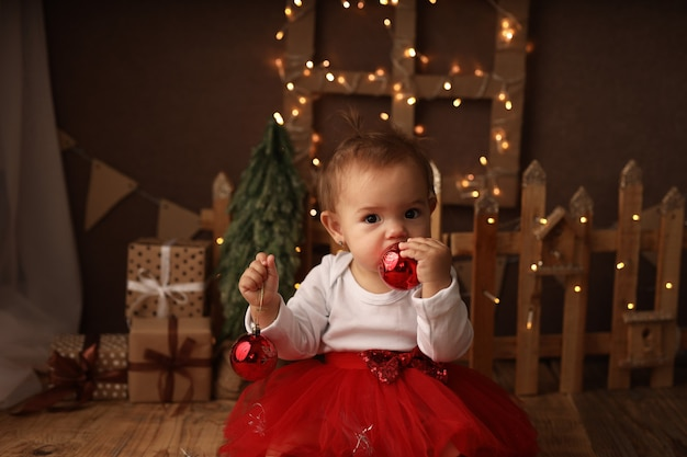 A cute little girl in a new years costume rejoices and plays with a red christmas ball