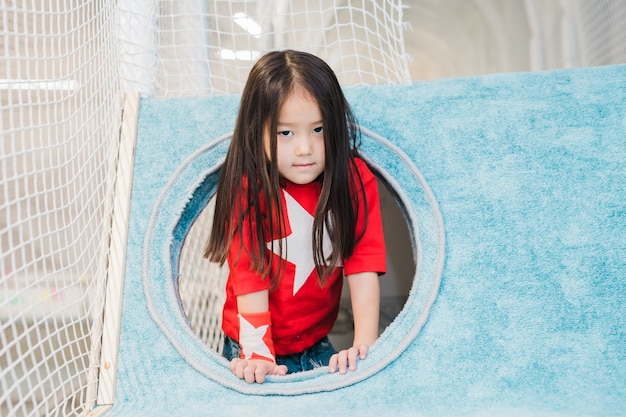 Милая маленькая девочка азиатской национальности в костюме супердевушки смотрит на вас, играя в мягком доме на игровой площадке