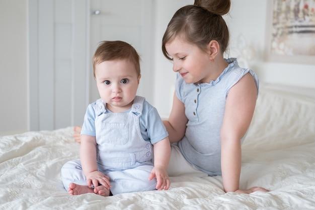 Милая маленькая девочка старшая сестра с ее маленьким братом мальчика дома, сидя на кровати