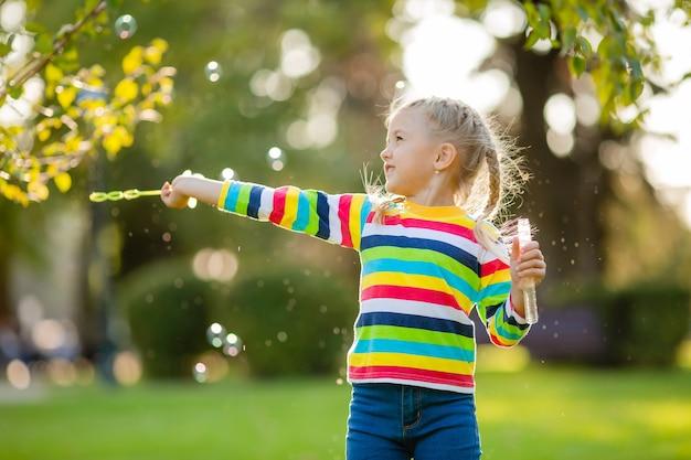Милая маленькая девочка на прогулке в разноцветной вязаной кофточке