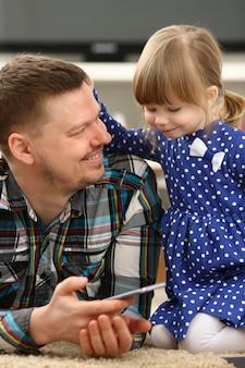 Милая маленькая девочка на ковер с папой и смартфоном