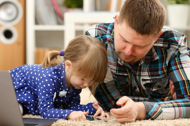 お父さんと一緒に床のカーペットの上でかわいい女の子は、お母さんの肖像画を呼び出す携帯電話を使用しています。ライフスタイルアプリソーシャルウェブネットワークワイヤレスipテレフォニーコンセプト