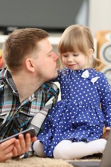 아빠와 함께 바닥에 귀여운 소녀는 엄마 초상화를 호출하는 핸드폰을 사용