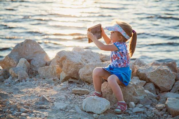 멋진 전망의 사진을 찍고 디지털 태블릿 바위 해변에 귀여운 어린 소녀. 아이는 일몰 또는 일출에 셀카를 만들고있다