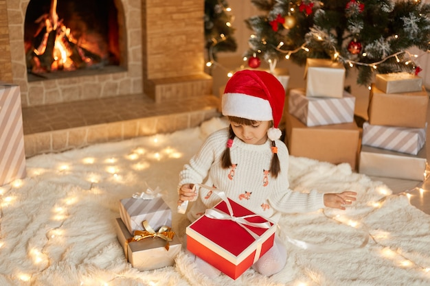 Cute little girl opening christmas gift at home while sitting on soft carpet on floor, looking at box, pulls ribbon to open present, dresses white pullover and red santa hat.