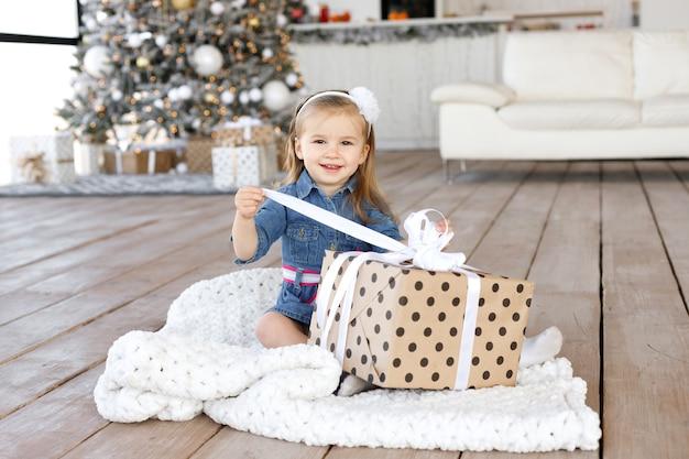 Милая маленькая девочка открывает свои рождественские подарки