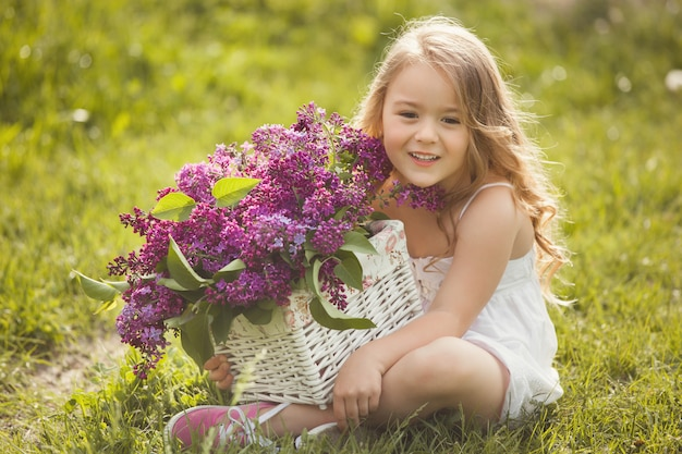 Cute little girl outdoors with spring flowers. pretty child with lilac bouquet summer time.