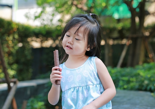 Cute little girl outside in nature eating chocolate bar