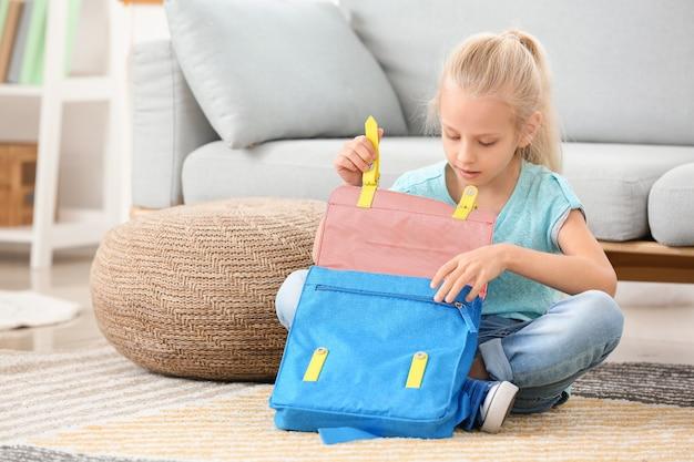 Милая маленькая девочка, упаковывающая школьный портфель дома