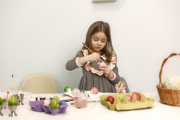 La bambina sveglia dipinge le uova. famiglia seduta a casa. prepararsi per la pasqua
