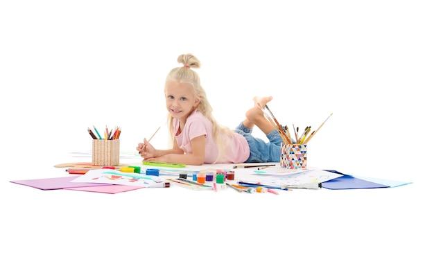 Милая маленькая девочка рисует на белом фоне