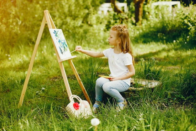 Cute little girl painting in a park