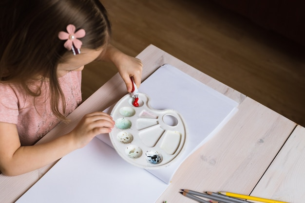 Cute little girl painting picture on home interior