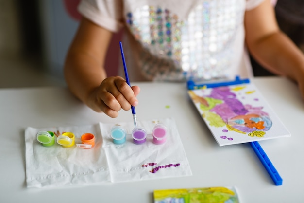 Cute little girl painting picture at home.