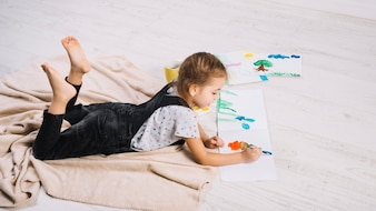 Cute little girl painting with bright aquarelle on floor