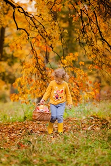 Cute little girl picking apples in a green grass background at sunny day