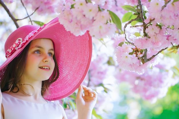 Cute little girl in pink hat spring teenager portrait