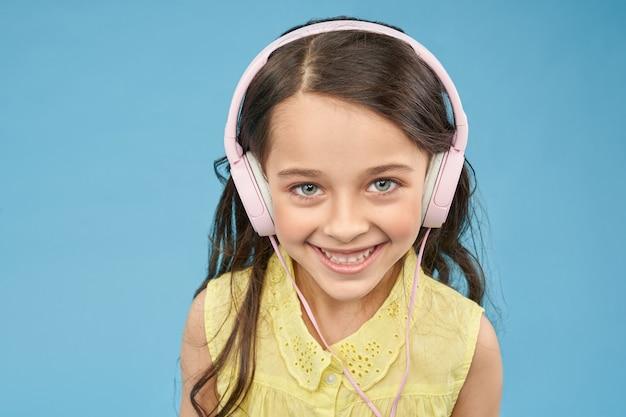 Cute little girl in pink headphones