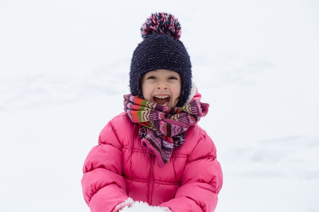 A cute little girl in a pink jacket and a hat is playing in the snow. winter children's entertainment concept.