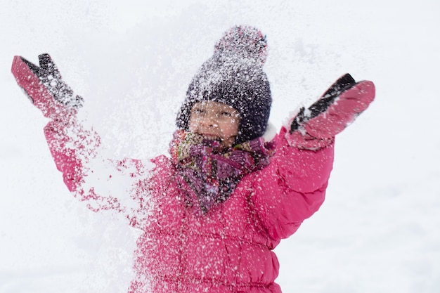 Una bambina carina con una giacca rosa e un cappello sta giocando nella neve. concetto di intrattenimento per bambini invernali.