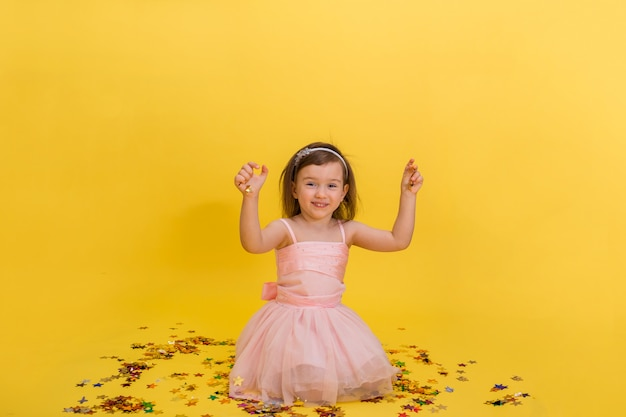 Cute little girl in a pink puffy dress is sitting and playing with confetti. birthday party.