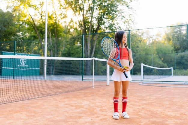 Милая маленькая девочка играет в бадминтон на открытом воздухе в теплый и солнечный летний день