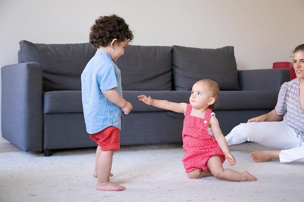 Bambina sveglia che gioca sul tappeto con un ragazzo misto. giovane mamma ritagliata che guarda i bambini e sorride. bambino riccio in piedi a piedi nudi nel soggiorno. famiglia al chiuso, weekend e concetto di infanzia