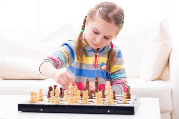 Cute little girl playing chess