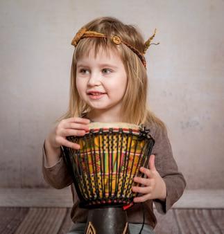 Милая маленькая девочка играет барабан