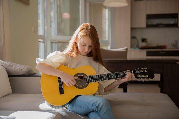 Милая маленькая девочка играет на гитаре