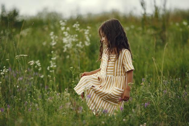 Милая маленькая девочка играет в летнем поле