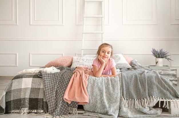 ベッドで遊ぶかわいい女の子。思慮深く見え、休む。