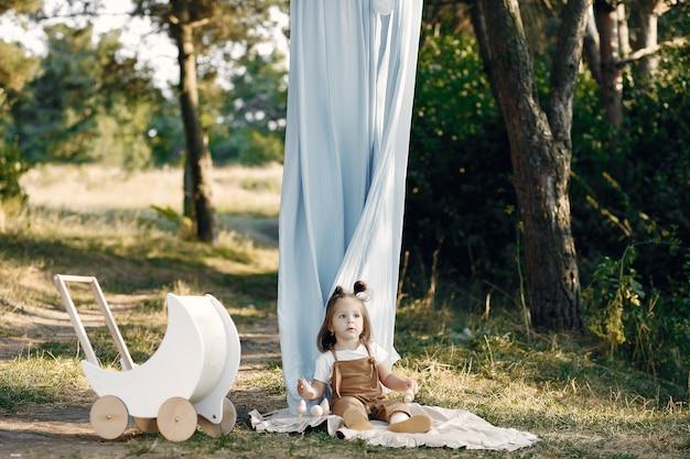 Bambina sveglia che gioca in un parco con il trasporto bianco