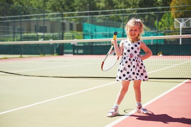 Милая маленькая девочка играет в теннис на теннисном корте снаружи.