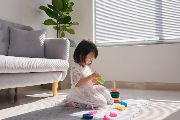 自宅の床でビルディングブロックで遊ぶかわいい女の子