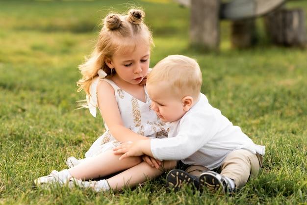 晴れた日に外で兄と遊ぶかわいい女の子
