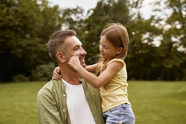 夏の日に公園を訪れている間、愛する父親と遊んでいるかわいい女の子が彼に触れています