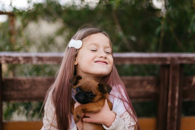 작은 갈색 강아지와 함께 노는 귀여운 소녀