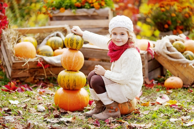 Cute little girl playing with pumpkins in autumn park. autumn activities for children. adorable  little girl builds a tower of pumpkins.  halloween and thanksgiving time fun for family.