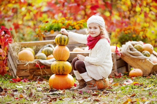 Cute little girl playing with pumpkins in autumn park. autumn activities for children. adorable  little girl builds a tower of pumpkins.